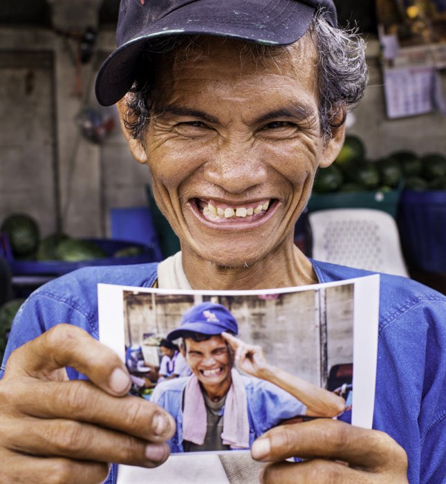 man holding a photo of himself smiling