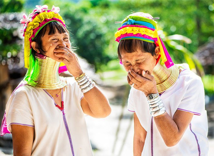 Two Kayan long neck women laughing together at Baan Thong Luang during a Chiang Mai Photo Workshop, Thailand, about Hill Tribe Tourism