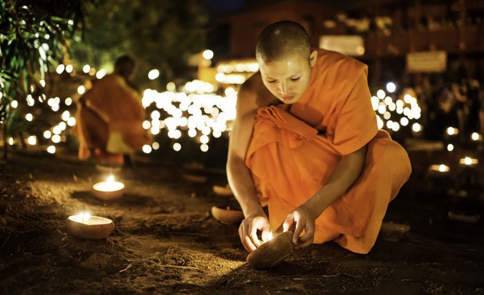 Buddhis monks light candles for an evening ceremony at a temple in Chiang Mai