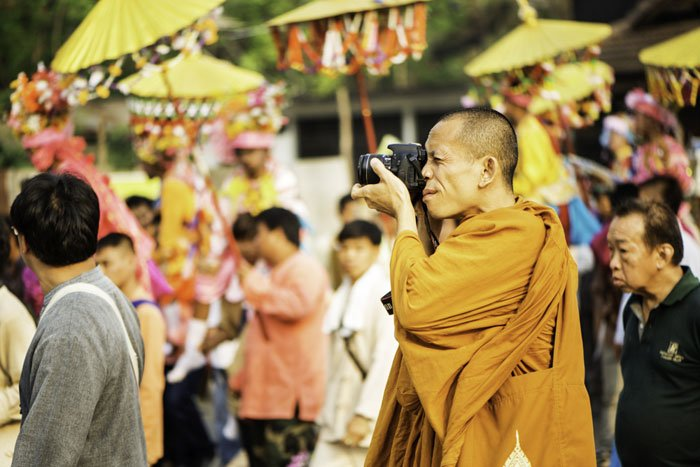 Buddhist monk taking a photograph with a DSLR camera