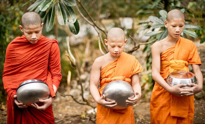 young novice monks receive alms in the morning
