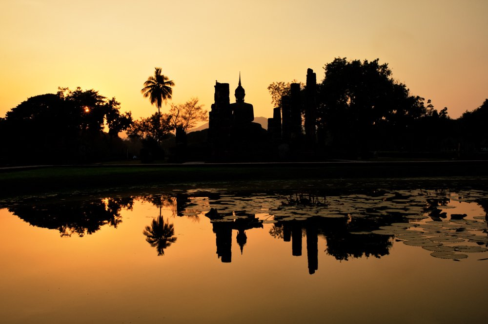 Temple ruins reflected in a pond at sunset at the UNESCO World Heritage Site, Sukothai, Thailand.