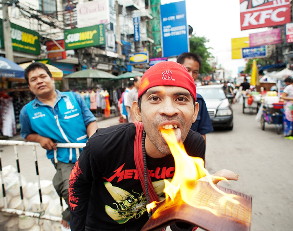 A street vendor in Khao San Road, Bangkok, demostrates to a group of tuktuk drivers and tourists that the product he is selling is genuine crocodile skin by pouring lighter fluid on the wallet and setting it on fire. How To Take the Best Pictures in Thailand